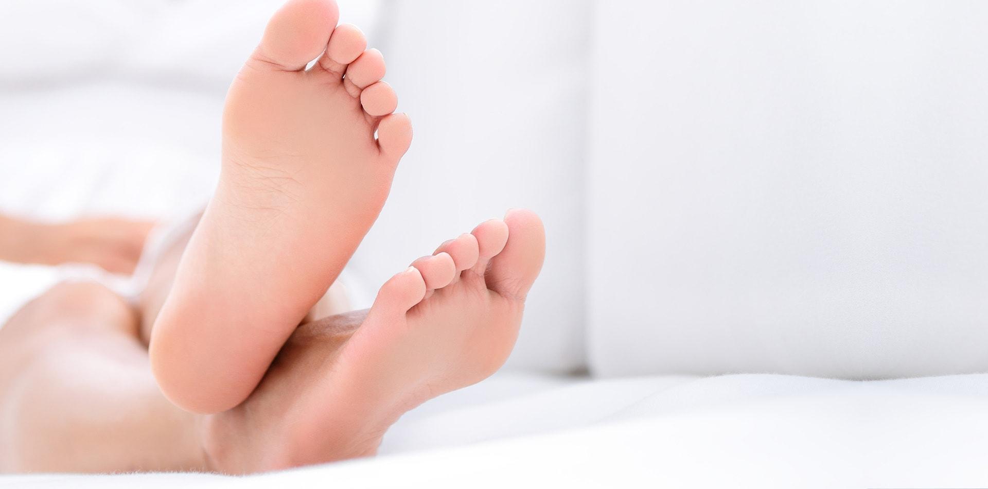 Woman feet closeup - barefoot woman relaxing sofa